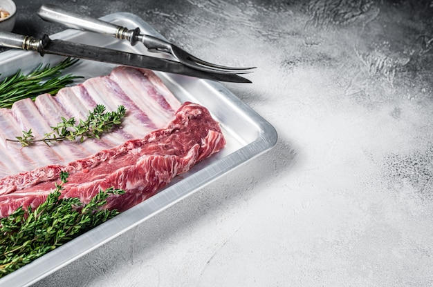 베이킹 접시에 양고기 양고기 갈비의 원시 요리하지 않은 랙. 흰색 배경. 평면도. 공간을 복사하십시오.