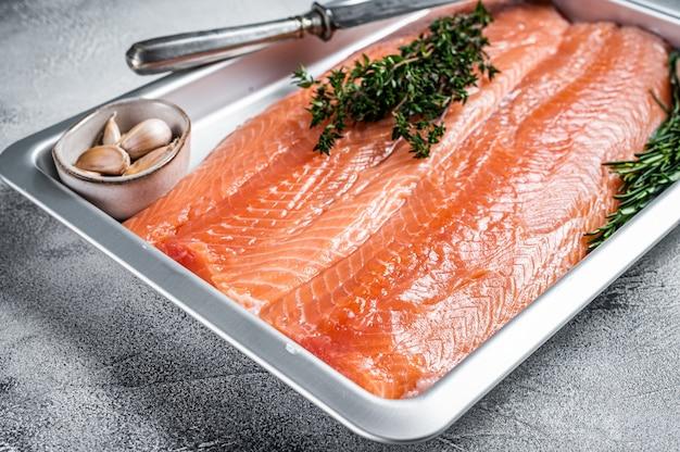 요리하지 않은 생 연어 필레 생선을 허브가 든 주방 쟁반에 있습니다. 흰 바탕. 평면도.