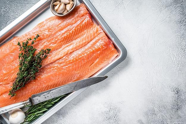 生の未調理のサケの切り身の魚をハーブと一緒にキッチントレイに入れます。白色の背景。