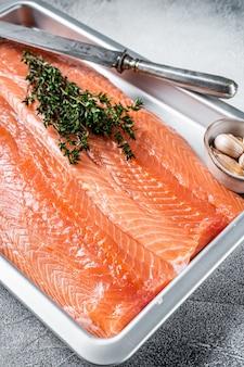 Сырое сырое филе морского лосося на кухонном подносе с зеленью