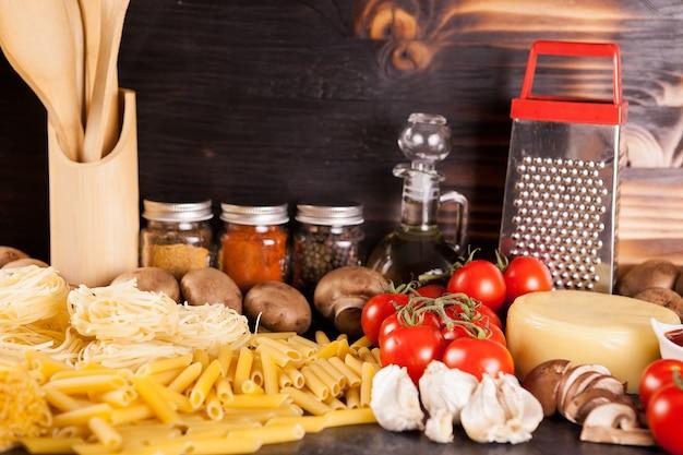 素朴な背景の新鮮な野菜の横にある生の生スパゲッティ、パスタ、マカロニ