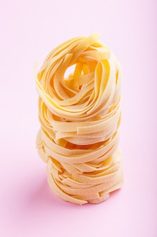 Raw uncooked tagliatelle pasta on a pink pastel background