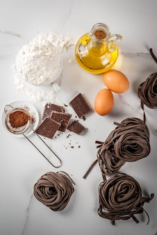 Raw unprepared chocolate pasta noodles with ingredients for cooking
