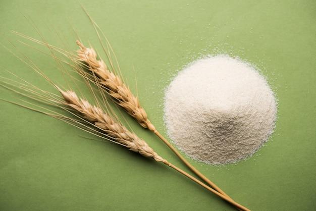 ボウルまたはスプーンでヒンディー語でravaパウダーとしても知られている生の未調製のセモリナ粉。白または不機嫌そうな背景に分離されたクローズアップ。セレクティブフォーカス