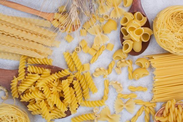 Varie forme di pasta crude e cucchiai su uno spazio bianco.