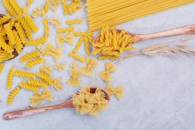 Varie forme di pasta crude e cucchiai su superficie bianca