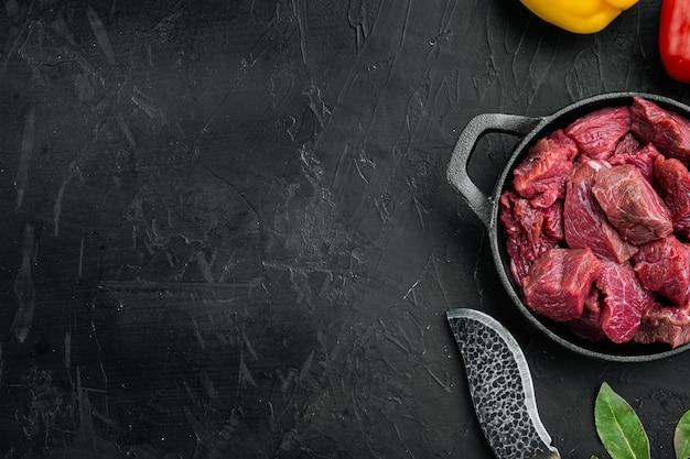 Сырая телятина для тушеного мяса, в чугунной сковороде, на черном каменном фоне, плоская планировка, вид сверху, с местом для текста