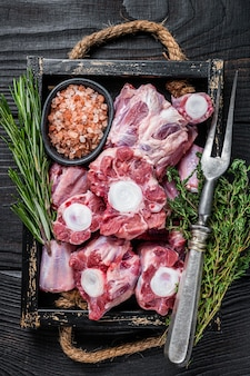 Сырая телятина из говядины из бычьего хвоста в деревянном подносе с тимьяном