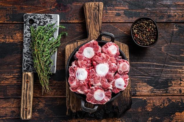 Сырая телятина из говядины из бычьего хвоста на деревянной доске мясника с тесаком