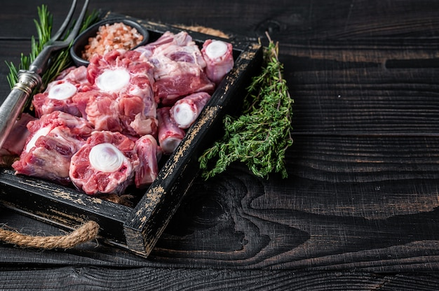 Raw veal beef oxtail meat in wooden tray with thyme