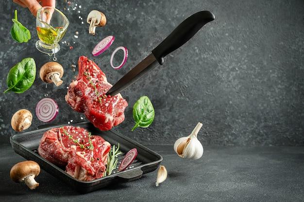 Сырой стейк из телячьей кости, падающий на сковороду для гриля с ингредиентами для приготовления на темном фоне
