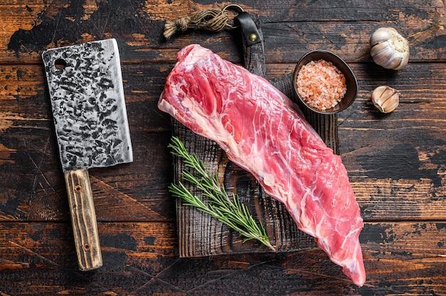 정육점 칼로 짧은 갈비에 생 송아지 고기 고기. 어두운 나무 배경입니다. 평면도.