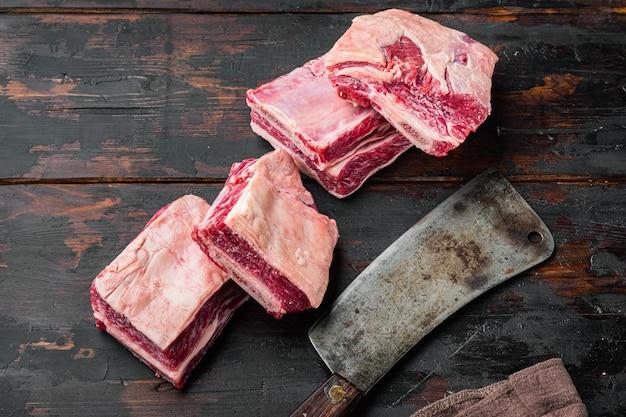 古い暗い木製のテーブルの上に、生の子牛の子牛のカルビ肉セットと古い肉切り包丁