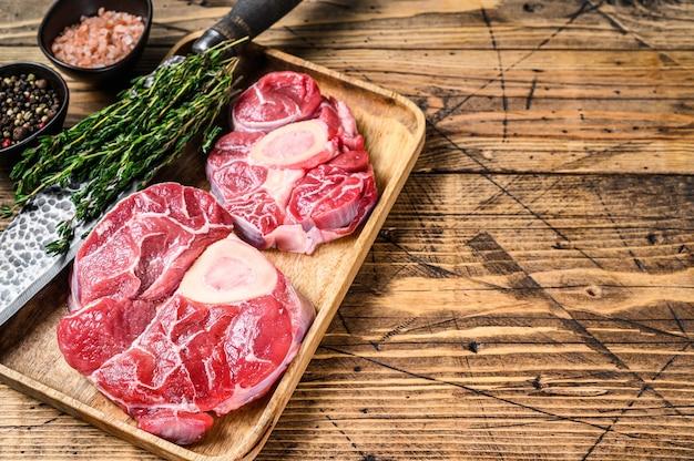 송아지 고기 크로스 컷 생크 고기 osso buco, 이탈리아 ossobuco 요리. 나무 배경입니다. 평면도. 공간을 복사하십시오.