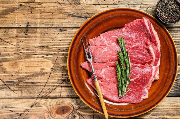 皿に生の子牛の肉チョップ ステーキ。