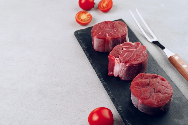 Raw veal medallions on black stone board close up