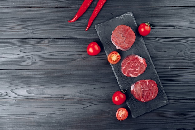 Raw veal medallions on black stone board