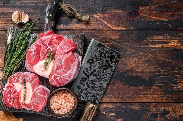 송아지 고기 생크 스테이크 고기 오소 부코, 이탈리아 오소부코 요리. 어두운 나무 배경입니다. 평면도. 공간을 복사합니다.
