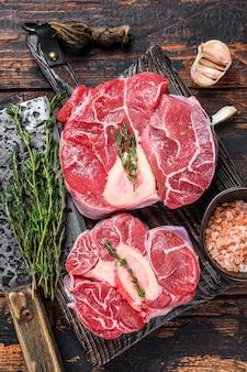송아지 고기 생크 스테이크 고기 osso buco, 이탈리아 ossobuco 요리. 어두운 나무 배경입니다. 평면도.