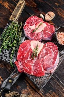 송아지 고기 생크 스테이크 고기 오소 부코, 이탈리아 오소부코 요리. 어두운 나무 배경입니다. 평면도.