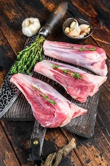 生の子牛のすね肉をまな板にハーブで添えます。暗い木製のテーブル。上面図。