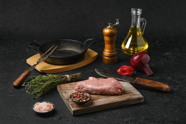 Стейк из сырой телятины с ингредиентами для приготовления на черном фоне