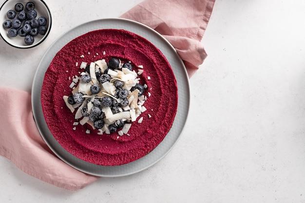 블루 베리와 코코넛 칩으로 장식 된 비건 생 비트 뿌리 케이크