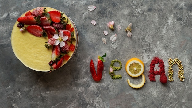 Raw vegan cake with fruit and seeds, decorated with flowers