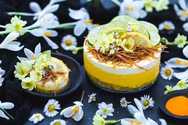 小さなデイジーの花で覆われた黒い表面にレモンとライムが入った生のビーガンケーキ