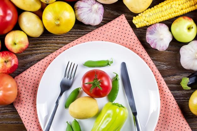 生のビーガンフードコンセプト。生野菜、カトラリー、木製の背景にナプキンプレート