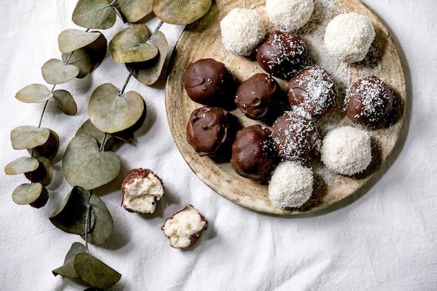 生のビーガン自家製ココナッツチョコレートキャンディーボール全体とユーカリの枝のある白い布地の背景の上にセラミックプレートのココナッツフレークで壊れた