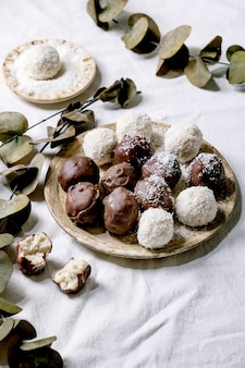 Raw vegan homemade coconut chocolate candy balls with coconut flakes in ceramic plate over white textile background with eucalyptus branches