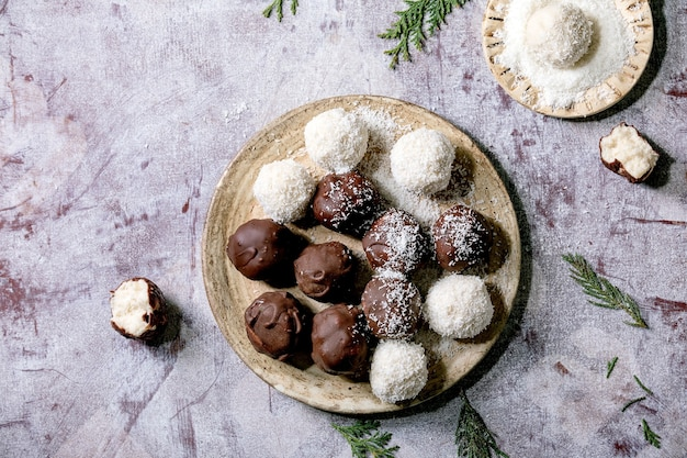 Raw vegan homemade coconut chocolate candy balls with coconut flakes in ceramic plate over white wooden background
