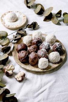 ユーカリの枝が付いている白い織物の背景の上のセラミックプレートのココナッツフレークと生のビーガン自家製ココナッツチョコレートキャンディーボール