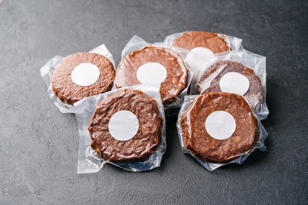 Raw vegan meatless cutlets in vacuum film, hamburger on a dark background. mockup sticker