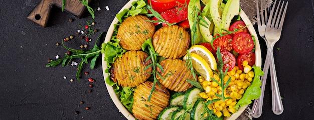 Сырые овощи и печеный картофель в миску.