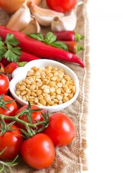 生野菜と白で隔離されるボウルに乾燥分割黄色エンドウ豆をクローズアップ