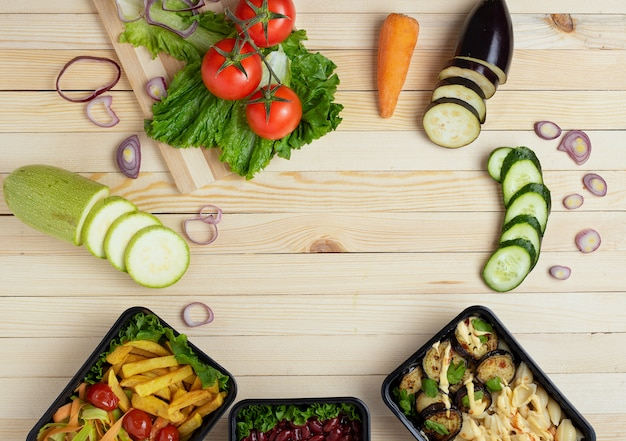 Raw vegetables around wooden table. black food containers with lunch and dinner. copy space