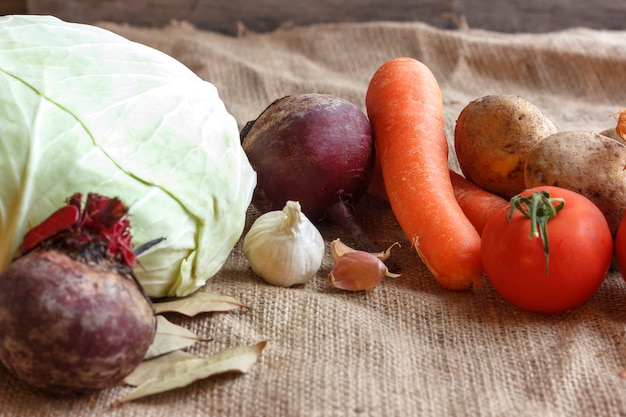 Raw vegetables for beet soup borscht. white cabbage, beet, carrot, potato, tomato, garlic on a wooden board