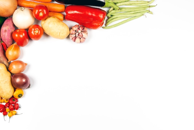 Raw vegetables on the corner over white background with copy space