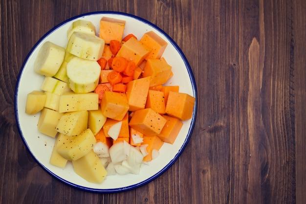 Сырые овощи для супа на белой тарелке
