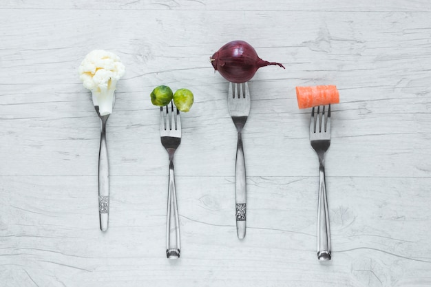 Raw vegetables on fork arranged in a row on wooden table