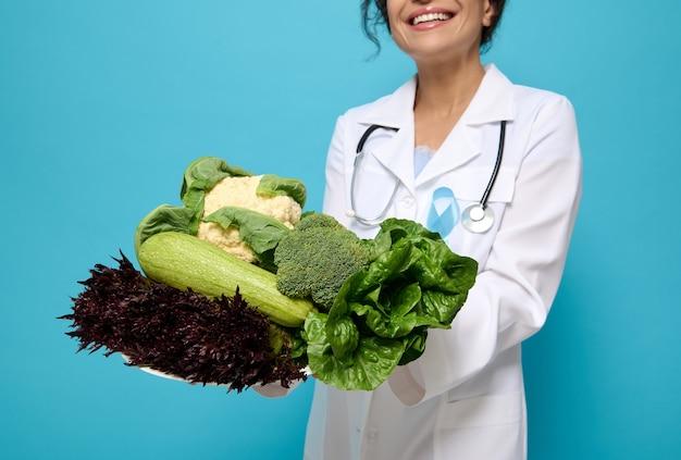 生野菜、健康的なビーガンフード、緑とサラダは、色付きの背景、コピースペースで隔離された青い糖尿病認識リボン付きの医療用ガウンを身に着けている笑顔の栄養士の手にあります。