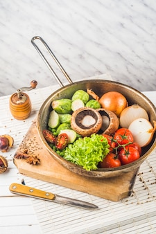 Сырые овощи в старой винтажной сковороде на разделочной доске