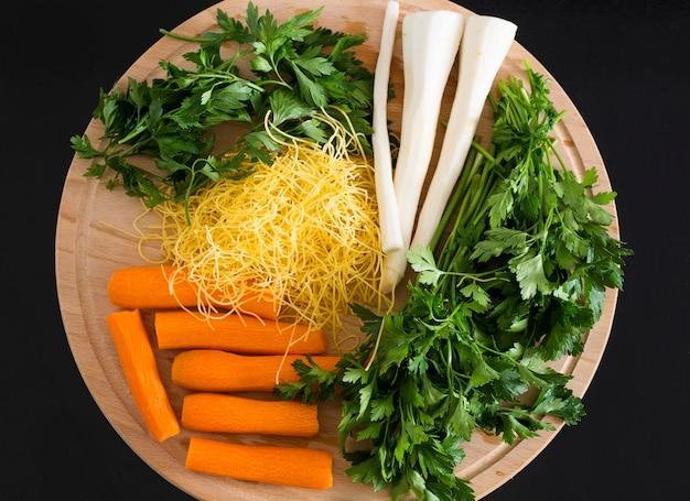 Сырые овощи на деревянном фоне.
