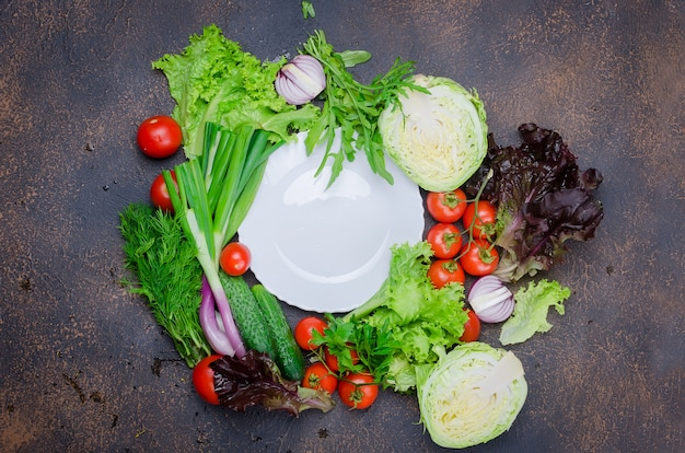 Raw vegetables for salad around plate