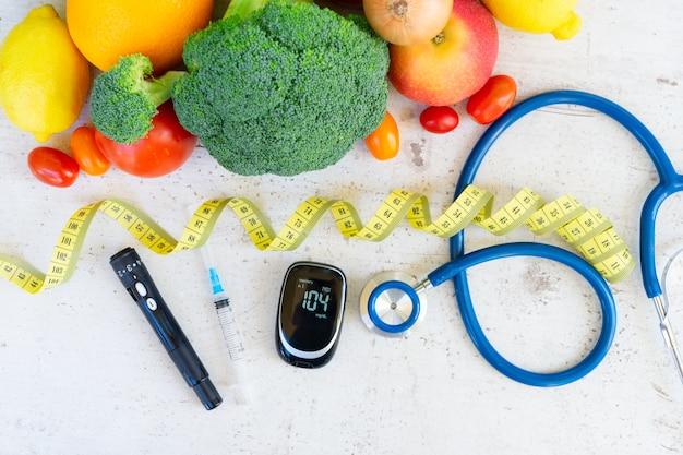 血糖値計、注射器、ランセット、聴診器を机の上に置いた生野菜、糖尿病の健康的な食事のコンセプト