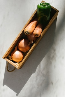 Raw vegetables in wooden tray on marble