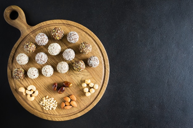 Raw vegetarian energy balls with cashews, hazelnuts, peanut butter and almond in the wooden board on the dark background. flat lay, close up, copy space.