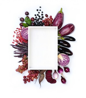 Raw violet vegetables and fruit around plate